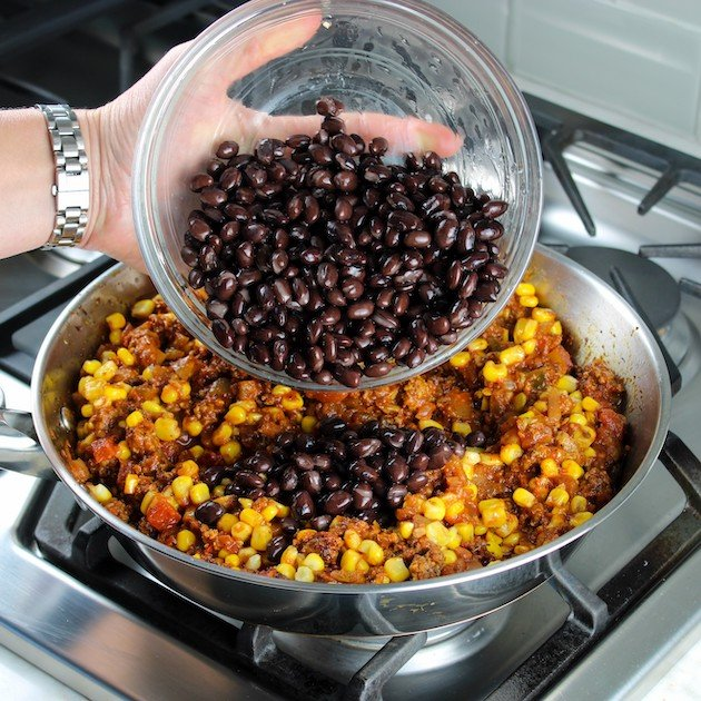 adding black beans to mexican lasagna filling