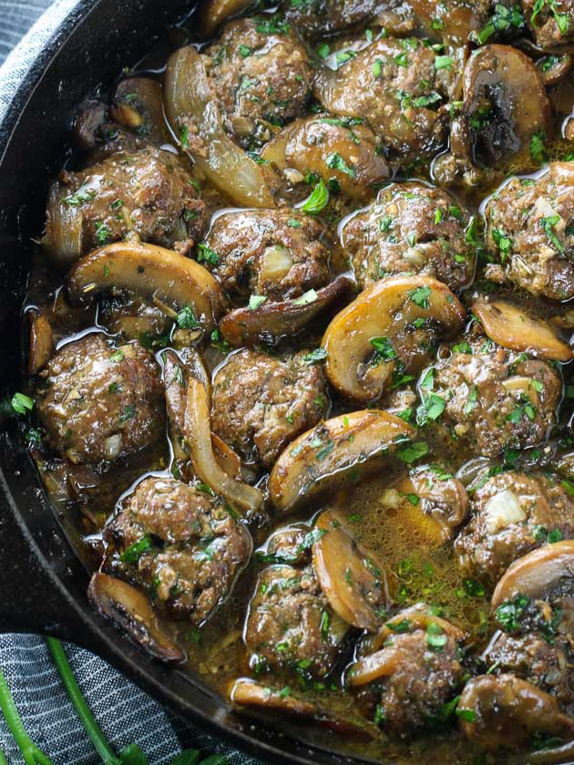 close up of skillet cooking meatballs and mushrooms