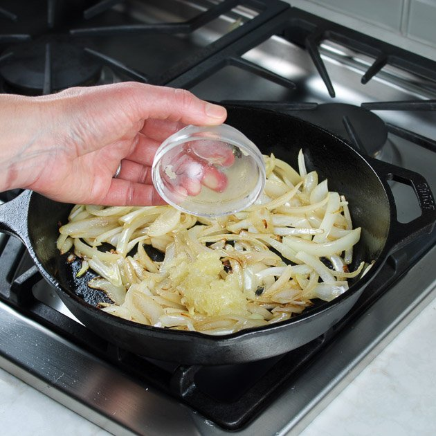 adding garlic to saute pan of onions