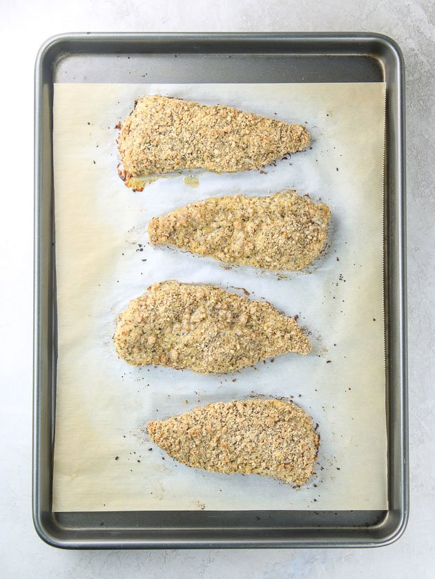 Breaded chicken cutlets on baking sheet after cooking