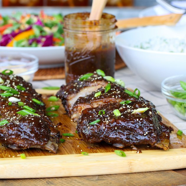 Racks of asian baby back ribs on cutting board with BBQ sauce and asian slaw in background