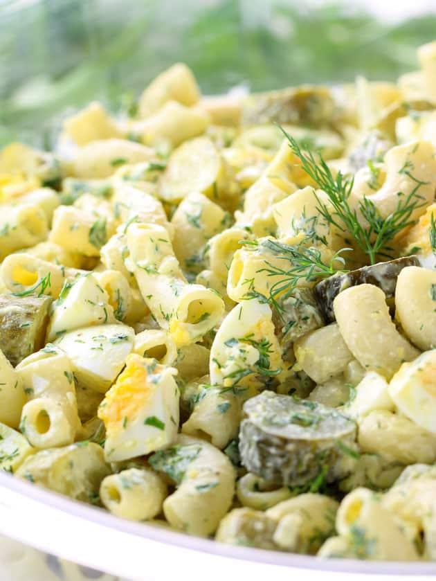 Close up macaroni salad in large glass mixing bowl