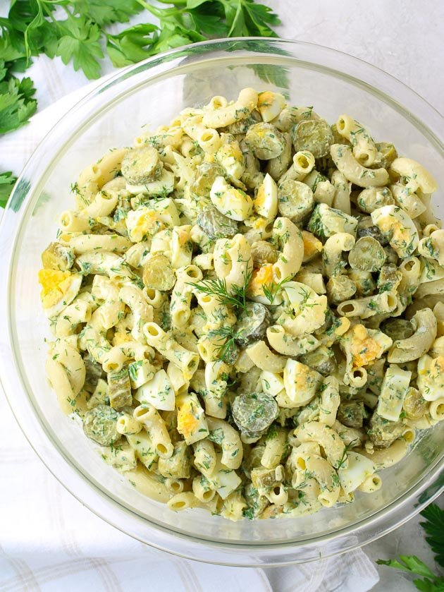 A bowl of Macaroni Pasta salad with pickles and dill