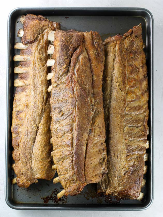 three racks of ribs on baking sheet after cooking