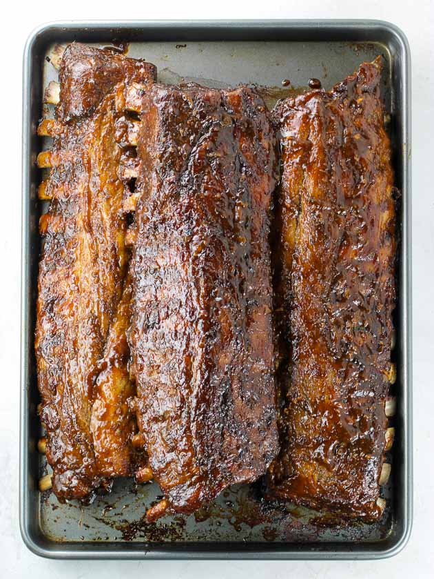 Three racks of ribs coated in barbecue sauce on a baking sheet