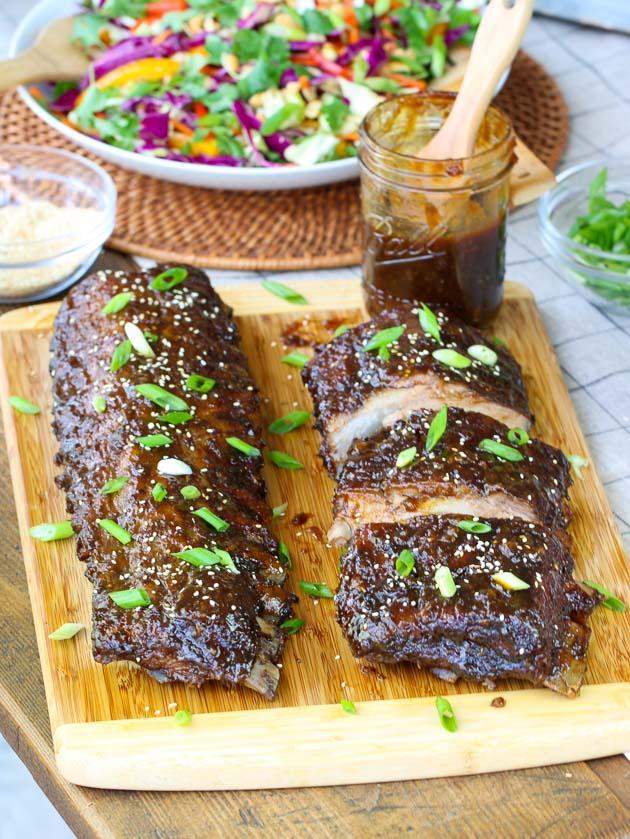 Two racks of ribs on cutting board with Mason Jar of sauce
