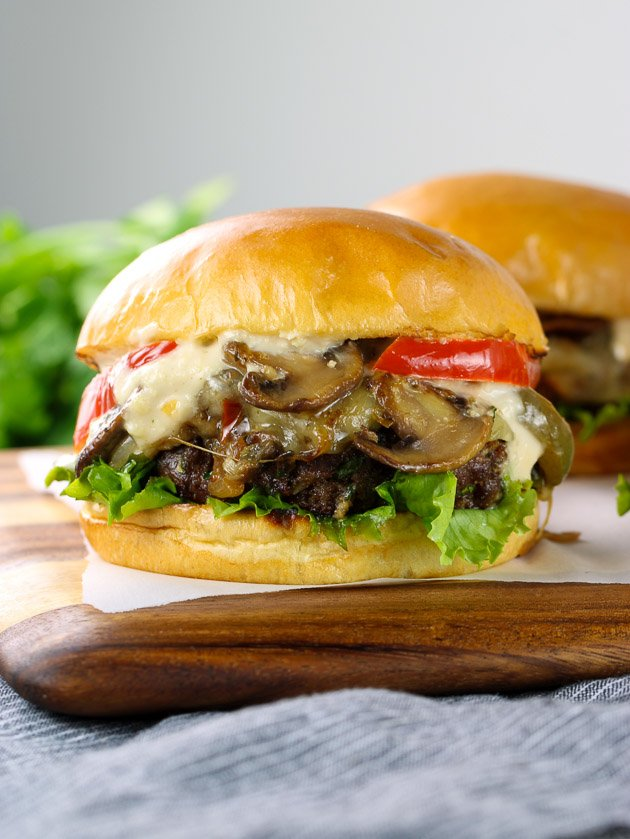 Cheese Steak Burgers with mushrooms, peppers, and cheese on a cutting board