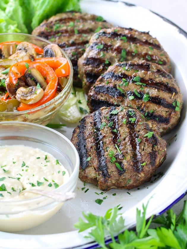 Grilled burgers on platter with cooked mushrooms and peppers and a bowl of Parmesan garlic aioli