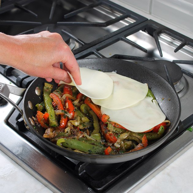Adding Provolone slices to saute pan with cooked peppers and mushrooms