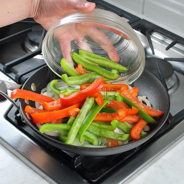 Adding sliced red and green peppers to saute pan