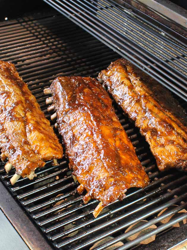 Three racks of ribs grilling