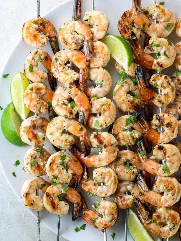 A large platter with 5 skewers of grilled shrimp