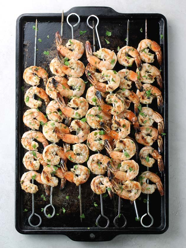 skewers of grilled shrimp on a baking sheet