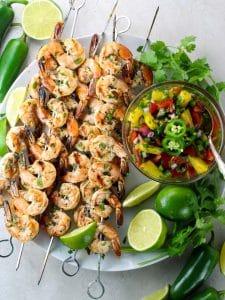 Shrimp skewers on platter with mango salsa