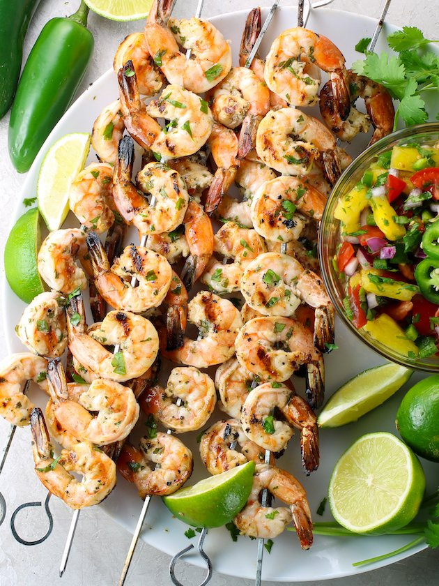 Shrimp skewers on platter with fruit salsa and limes