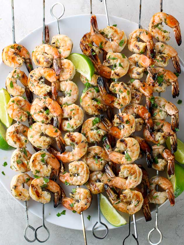 Shrimp skewers on platter with Limes and cilantro