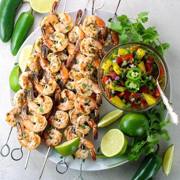 platter of shrimp skewers with salsa