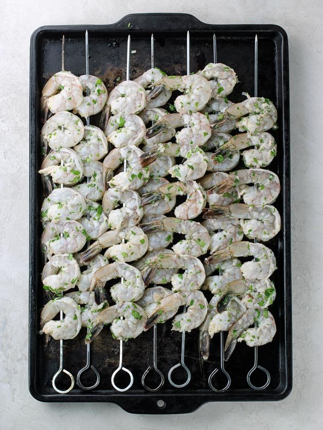 7 skewers of shrimp on a baking sheet ready to grill