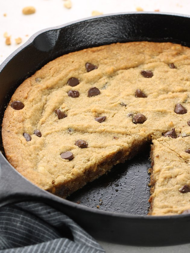 Close up partial skillet with a piece of the peanut butter chocolate chip cookie removed