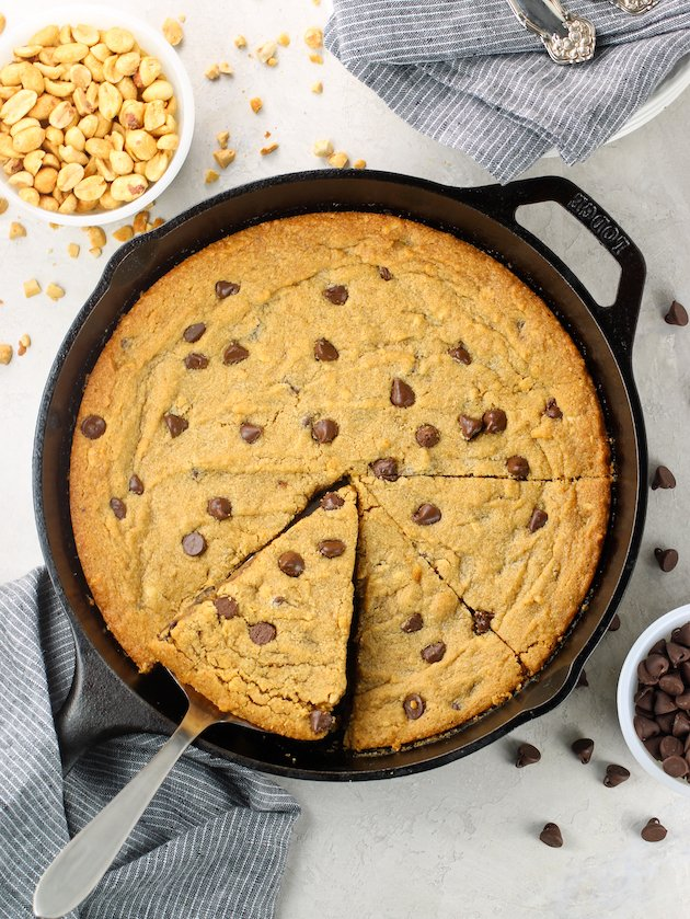 Cast iron skillet with peanut butter chocolate chip cookie and side dish of peanuts