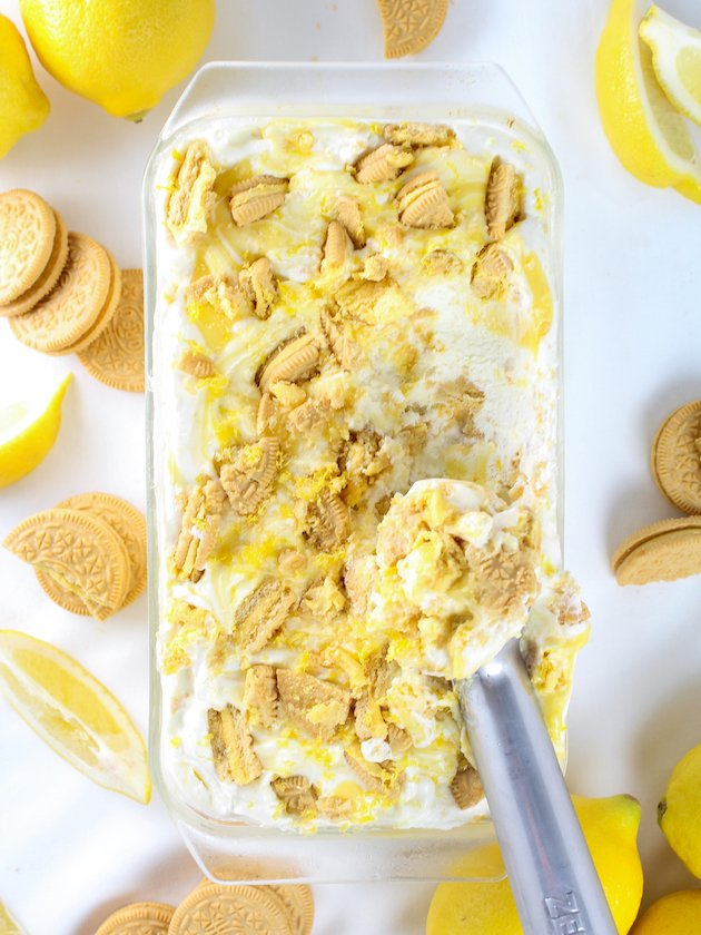 Glass loaf pan with lemon curd ice cream surrounded by fresh lemons and lemon oreos