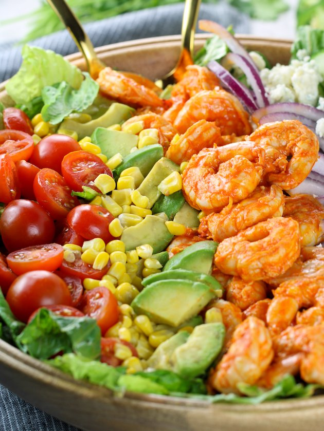 Partial dish eye level buffalo shrimp salad with gold serving utensils