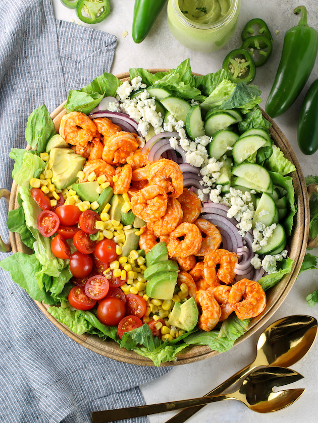 Fresh veggie buffalo shrimp salad in large wooden serving bowl with jalapenos and mason jar of dressing
