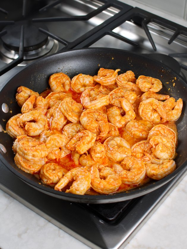 Saute pan full of buffalo shrimp cooking on stovetop