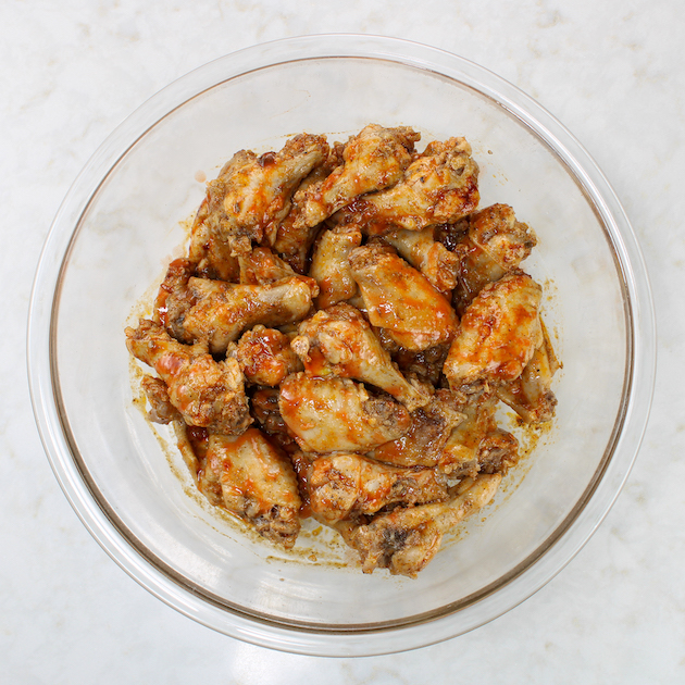Cooked chicken wings in glass bowl covered with red hot sauce