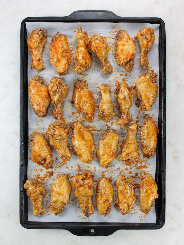 Buffalo wings lined up on parchment-covered baking sheet
