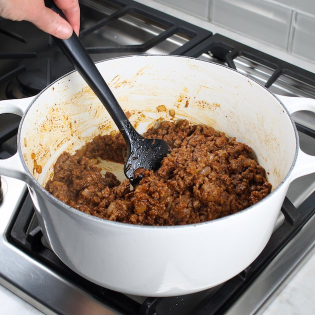 Stirring hamburger meat in a large white pot for cheesburger macaroni