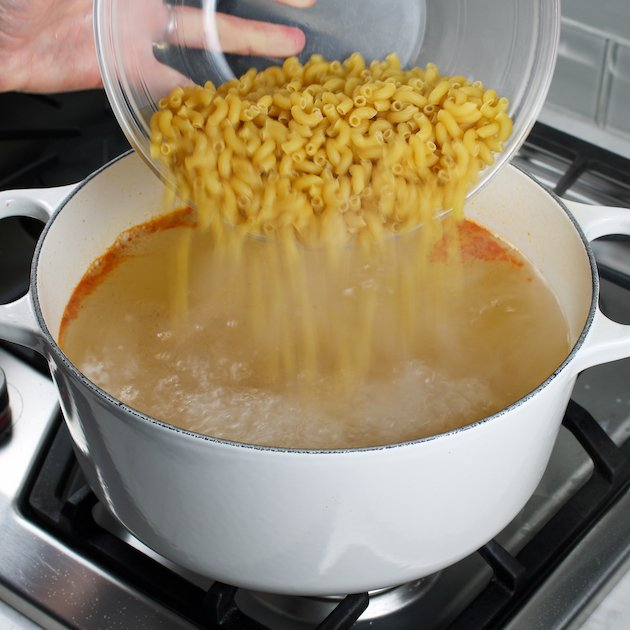 Pouring elbow macaroni into a pot of boiling water