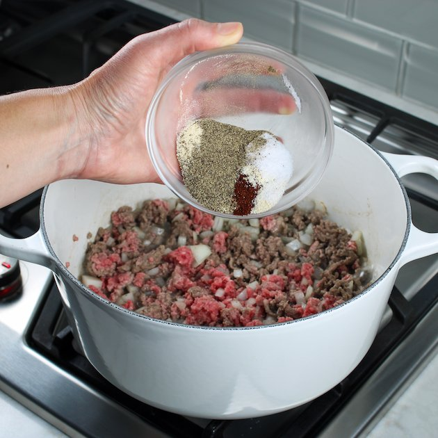 A woman's hand pouring seasonings into a pot of ground beef and onions