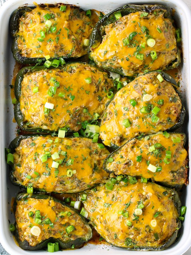 Casserole dish full of stuffed poblano peppers with melted cheese