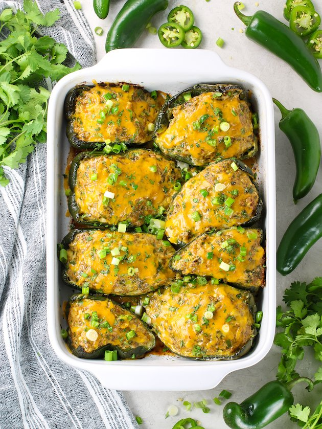 Casserole dish on table with baked stuffed poblano peppers