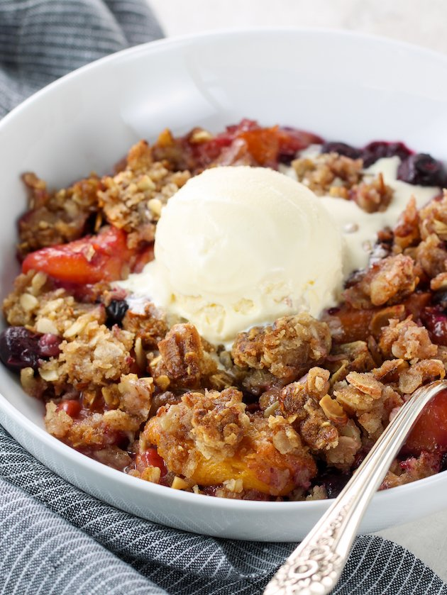 Eye level bowl of blueberry peach crumble with vanilla ice cream