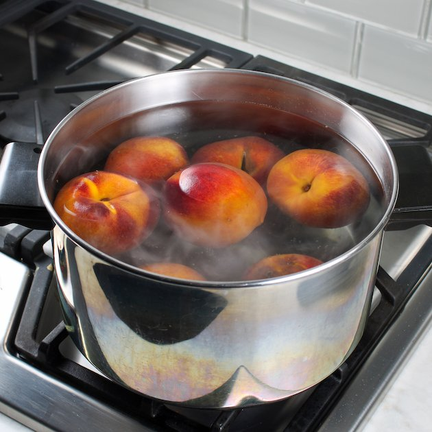 Pot of hot water on stove with peaches cooking