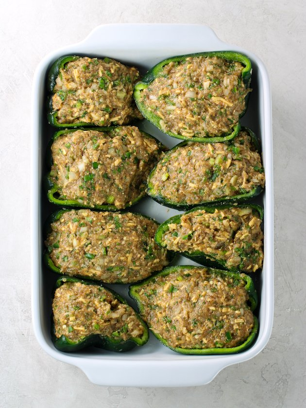 Baking dish with chicken stuffed poblanos before cooking