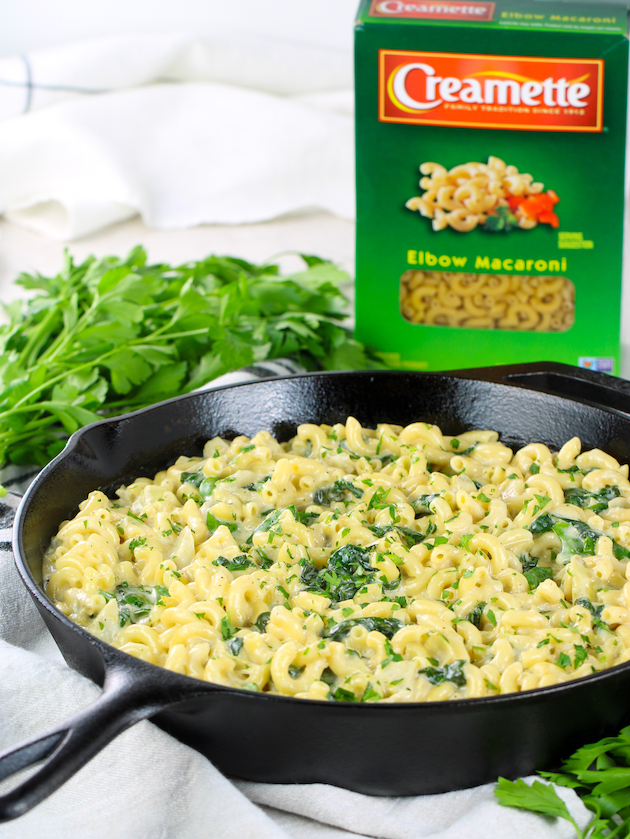 eye level skillet of spinach artichoke macaroni and cheese