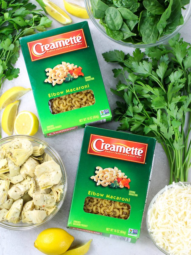 boxes of elbow macaroni table with bowls of spinach, artichokes, and cheese