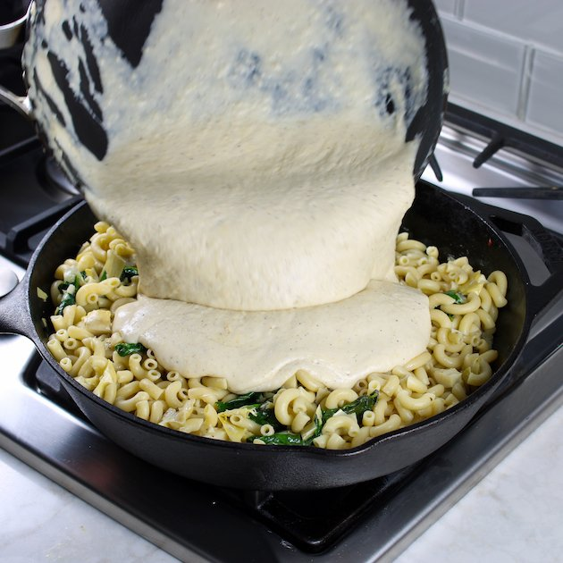 Adding cheesy sauce to mac and cheese skillet