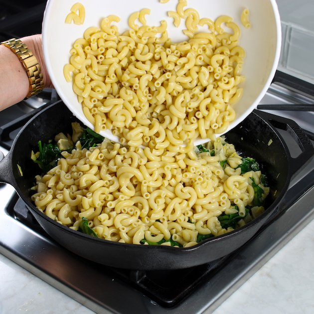 Adding cooked pasta to skillet with artichokes and spinach