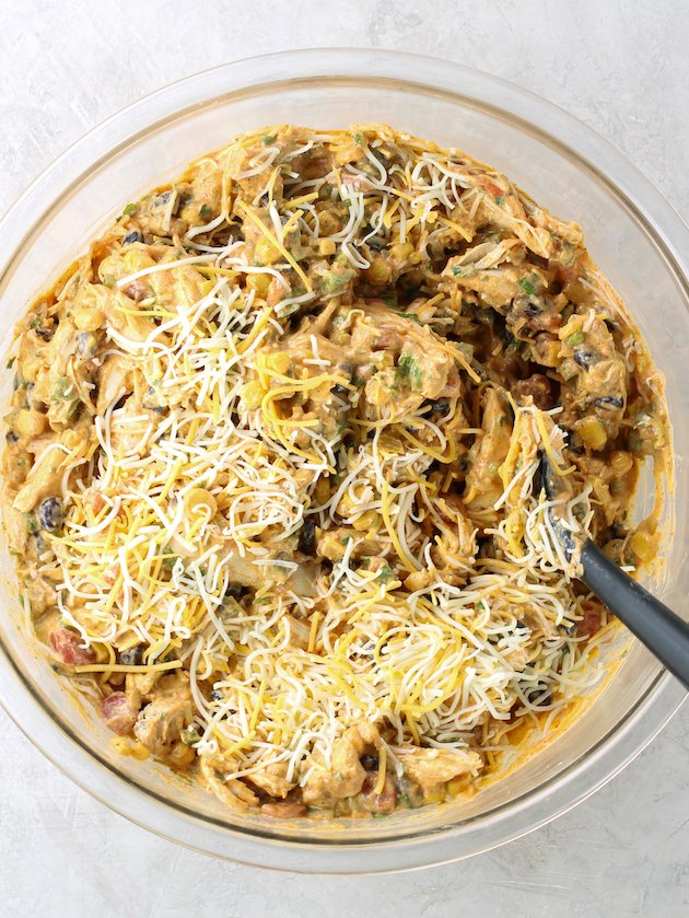 Adding shredded cheese into mixing bowl of chicken enchilada filling