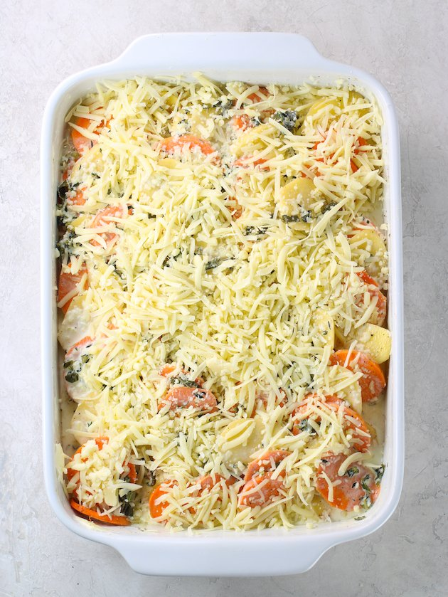 Casserole dish full of sliced yukon gold and sweet potatoes topped Gruyere cheese before cooking