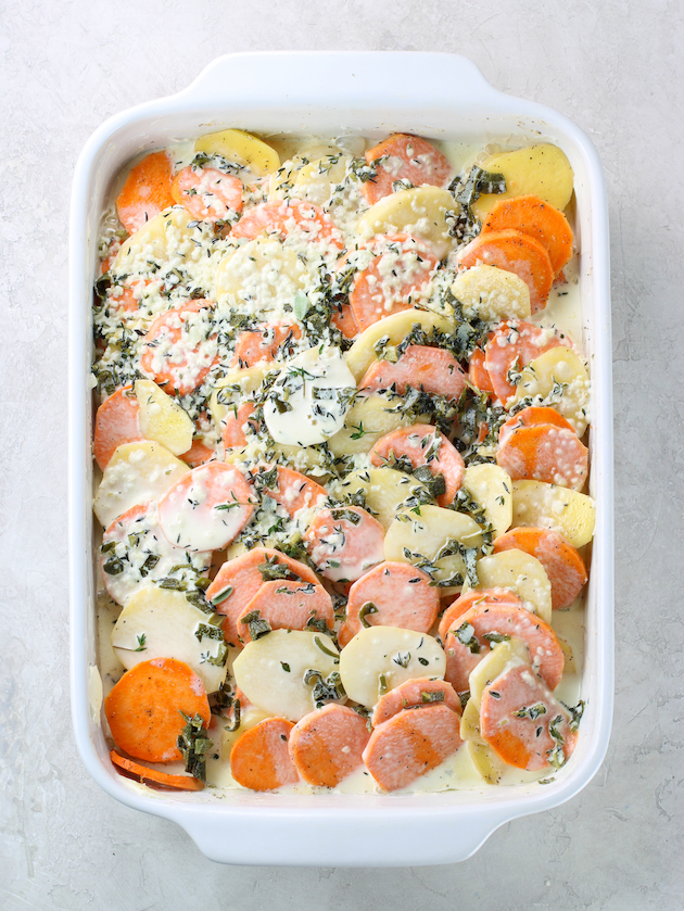 Casserole dish full of sliced yukon gold and sweet potatoes topped with cream sauce before cooking