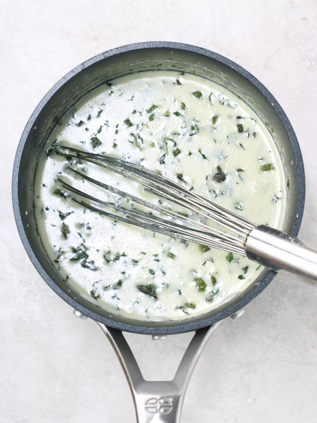 small pot of cream and herbs with wire whisk