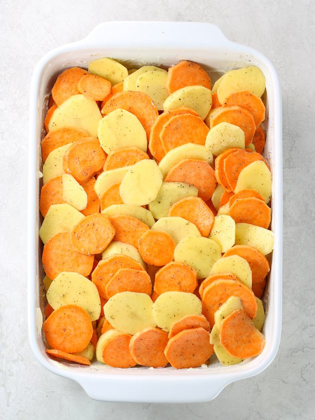 Casserole dish full of sliced yukon gold and sweet potatoes before cooking