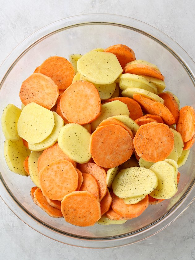 large glass bowl full of sliced sweet potatoes and gold potatoes