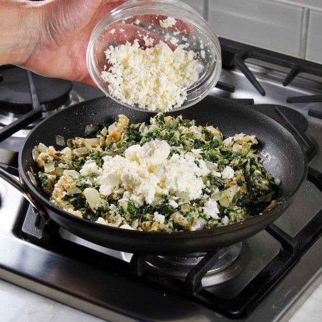 Adding feta to saute pan with spinach, onion, and garlic