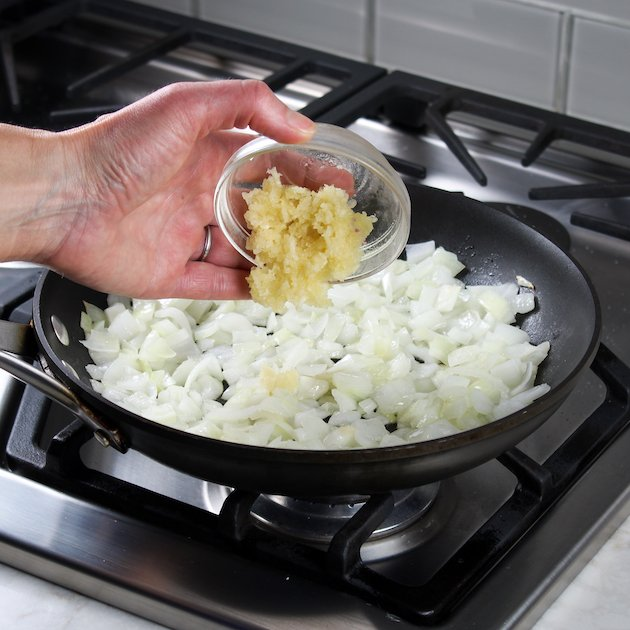 Adding minced garlic to onions in a saute pan